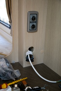 Installing an electric towel rail in a caravan - The feed for the towel rail is pulled through to an existing 13 amp socket
