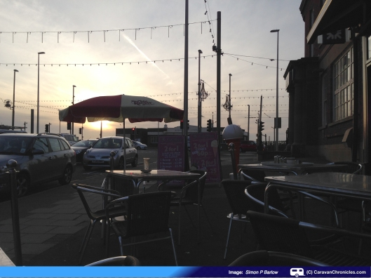 """Setting sun over cafe umbrella"""